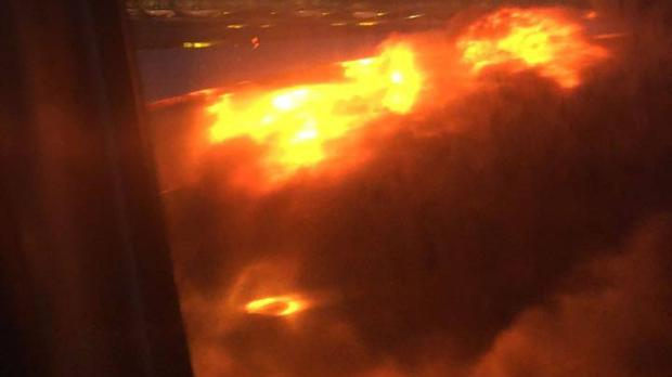 An engine on fire on a Singapore Airlines flight (Lee Bee Yee via AP)