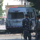 Lebanese policemen stand guard around a damaged ambulance in Qaa following a suicide bomb attack (AP)