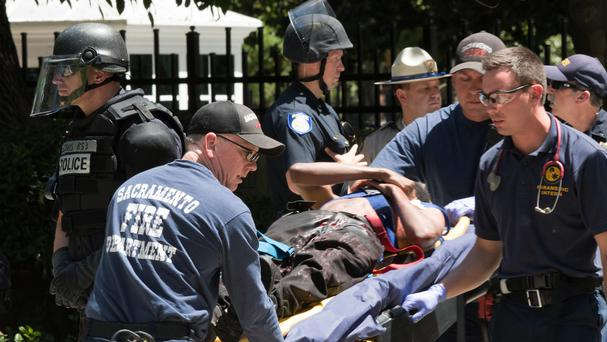 Paramedics tend to a stabbing victim after members of right-wing extremists groups holding a rally outside the California state Capitol building in Sacramento clashed with counter-protesters (AP)