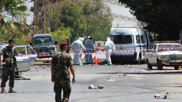 Lebanese soldiers stand guard as investigators inspect the scene next to a damaged ambulance that was attacked by one of the suicide bombers in Qaa (AP)