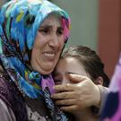Family members cry outside the Forensic Medical Centre in Istanbul (AP)