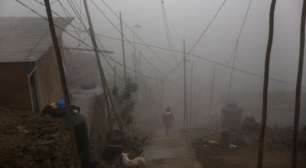 A resident walks down steps in thick fog in the Villa Maria del Triunfo district on the outskirts of Lima, Peru (AP)