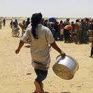 Syrian refugees gather for water at Ruqban border camp in north-east Jordan (AP)
