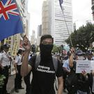 Protesters wave Hong Kong colonial flags as hundreds march during an annual pro-democracy protest in Hong Kong (AP)