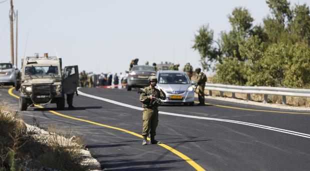 Israeli soldiers secure the scene of a shooting attack near Hebron (AP)