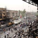 Iraqi security forces and civilians gather at the site after a car bomb hit Karada (AP)