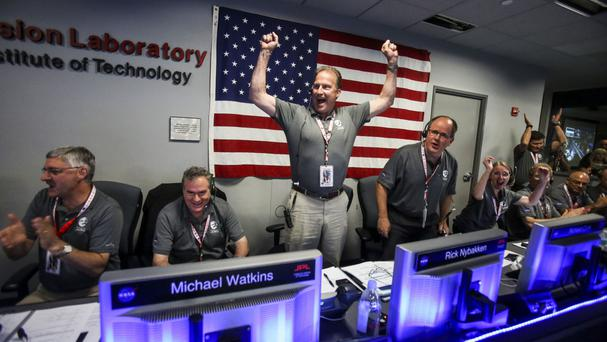 Scientists celebrate in Mission Control at Nasa's Jet Propulsion Laboratory as the solar-powered Juno spacecraft goes into orbit around Jupiter (AP)