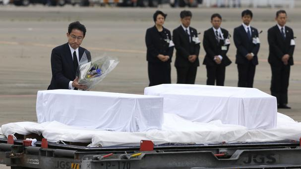 Japanese Foreign Minister Fumio Kishida lays flowers on the coffins of victims of the attack in the Bangladeshi capital Dhaka (AP)