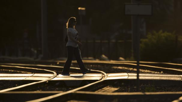 A woman crosses tracks during a 24-hour strike by railway workers in Greece (AP)