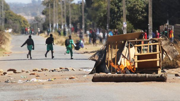Schoolchildren run past a burning barricade, following a job boycott called via social media platforms, in Harare (AP)