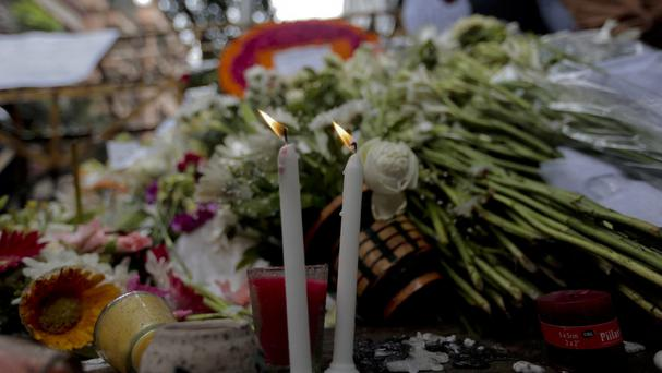 People offer flowers and light candles to pay their respects to the victims of the hostage crisis in Dhaka (AP)