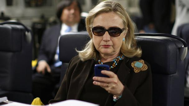 Hillary Clinton, pictured in 2011 when she was Secretary of State, checking her Blackberry inside a C-17 military plane bound for Libya (AP)