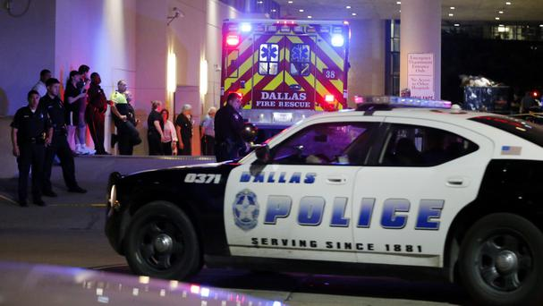 A Dallas police vehicle follows an ambulance carrying a patient to hospital during the shootings in the city (AP)
