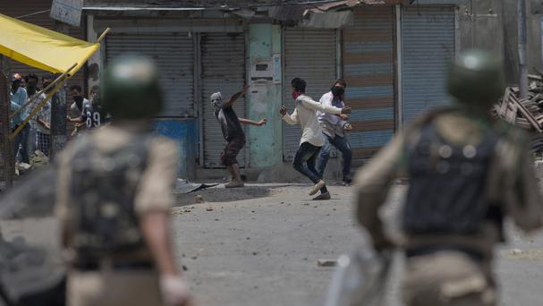 Kashmiri Muslim protesters throw bricks and rocks at Indian paramilitary soldiers in Srinagar (AP)