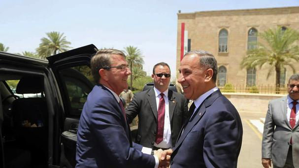 Visiting US defence secretary Ash Carter, left, shakes hands with Iraqi defence minister Khaled al-Obeidi in Baghdad (AP)