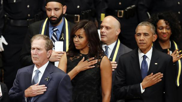 Former president George W Bush, first lady Michelle Obama and President Barack Obama stand during a memorial service for the fallen police officers in Dallas (AP)