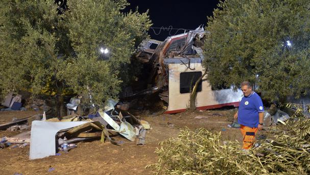 Rescuers work at the scene where two commuter trains collided head-on near the town of Andria, in the southern region of Puglia (AP)
