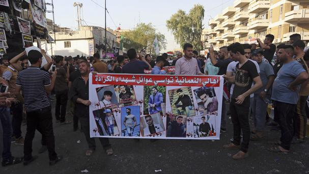 People hold a poster with pictures of civilians killed in a massive suicide truck bomb attack in Karada, Iraq (AP)