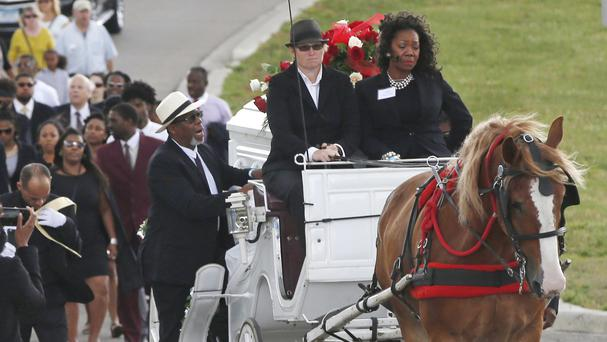 Valerie Castile, right, rides in the horse-drawn carriage with the casket of of her son, Philando Castile, during the procession to the Cathedral of Saint Paul in Minnesota.