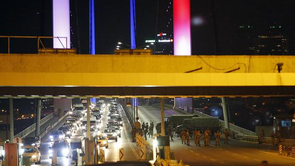 Turkish soldiers block Istanbul's iconic Bosporus Bridge, lit in the colours of the French flag in solidarity with the victims of the attack in Nice (AP)