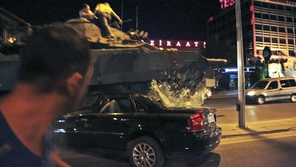 A tank drives over a car as Turkish people attempt to stop the attempted coup in Ankara (AP)