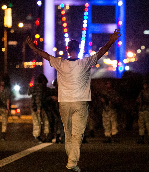 A man approaches Turkish military with his hands up at the entrance to the Bosphorus bridge. Photo: PA Getty