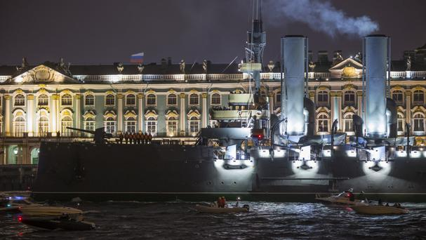 Tug boats tow the Aurora past the Winter Palace along the Neva River in St Petersburg, Russia (AP)