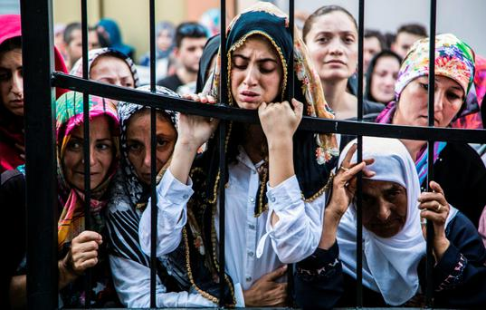 Women watch the funeral of a victim of the failed coup. Photo: Getty
