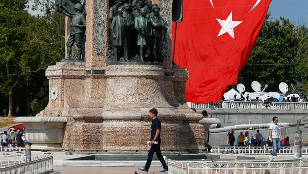 A man walks past Taksim Monument in Istanbul, Turkey, as warplanes continue to patrol the skies following Friday's failed coup (AP)
