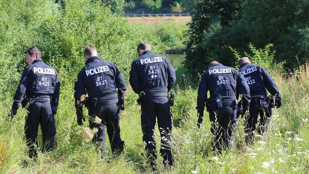 Police officers search for traces near the crime scene where a 17-year-old man from Afghanistan was shot (Karl-Josef Hildenbrand/dpa/AP)