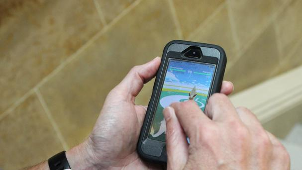 A gamer plays Pokemon Go on his smartphone (AP)