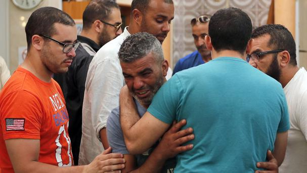 Tahar Mejri, centre, father of Kylan Mejri, is comforted by relatives at the ar-Rahma mosque in the eastern Nice suburb of Ariane (AP)