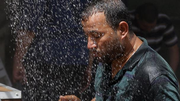 An Iraqi man cools off in an open-air shower in Baghdad as temperatures rise above 50C (AP)