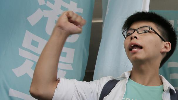 Joshua Wong shouts slogans outside a magistrates' court in Hong Kong (AP)