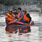 Rescuers use a raft to transport people along a flooded street in Shenyang in China's Liaoning Province (Chinatopix/AP)