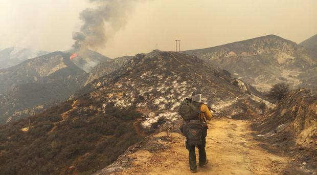 A large plume of smoke from a wildfire rises near Highway 1, burning five miles south of Carmel, California (AP)