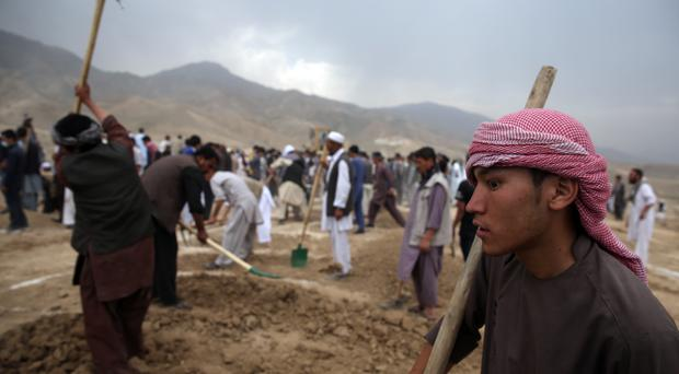 Afghan men dig graves for victims of a suicide attack in Kabul on Sunday July 24 (AP)