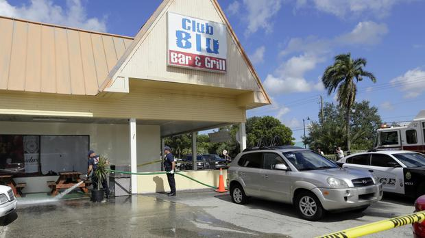 Firefighters hose down the pavement at the scene of a deadly shooting outside the Club Blu nightclub in Fort Myers, Florida (AP)
