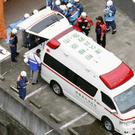Ambulance crews and firefighters outside the centre (Kyodo News/AP)