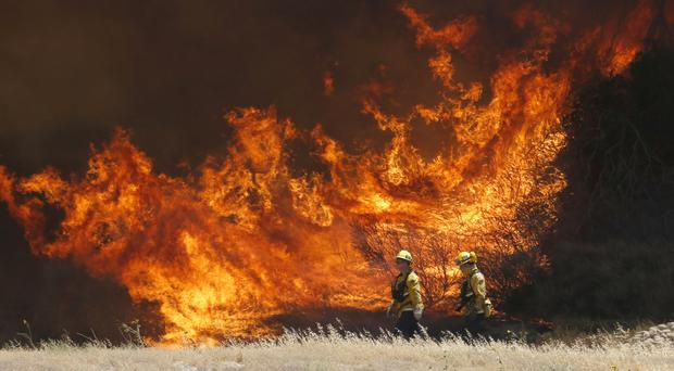 A hillside erupts in flame as a wildfire burns in Placerita Canyon in Santa Clarita (AP)