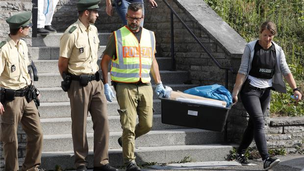 Police officers leave a former hotel where a 27-year-old Syrian man who had been denied asylum lived before blowing himself up in Ansbach, Germany (AP)