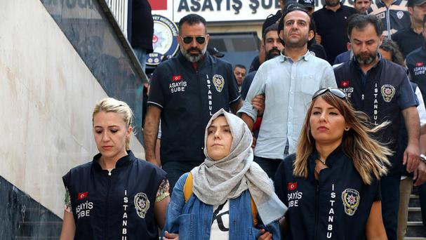 Police escort journalists to court in Istanbul as part of a sweeping crackdown (AP)