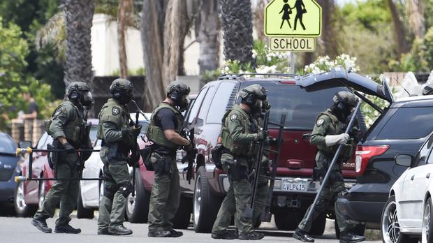 San Diego Police Swat officers prepare to enter a house with a possible suspect inside (AP)