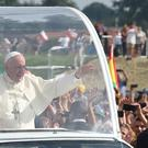 Pope Francis greets the faithful as he arrives to celebrate mass in Brzegi (AP)