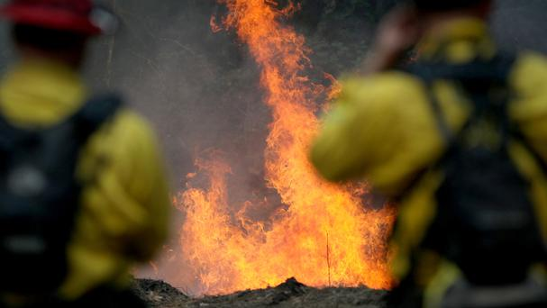 Firefighters monitor a burning section of a wildfire on the Garzas Trail in the Santa Lucia Preserve above Carmel Valley, California (Monterey County Weekly/AP)