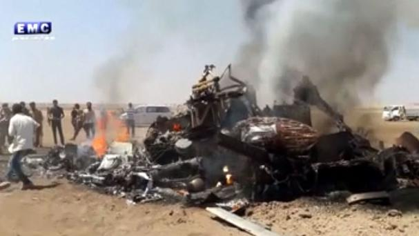 This image made from video provided by Thiqa news agency purports to show people gathered around the burning wreckage of a Russian helicopter downed in Syria (Thiqa News Agency via AP)