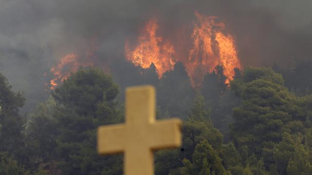 A fire burns over the Galataki Monastery near the village of Limni on the island of Evia (AP)