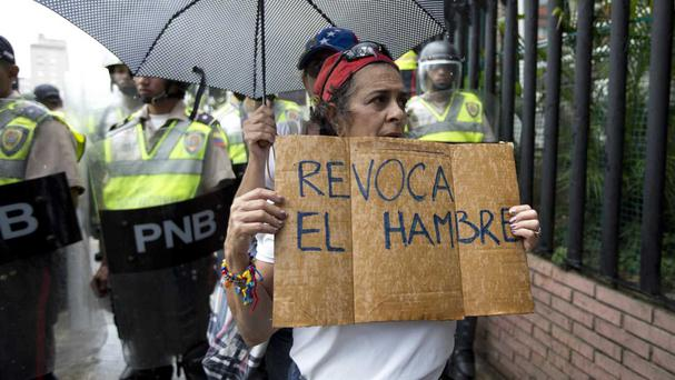 A woman holds a sign with a message that in reads in Spanish
