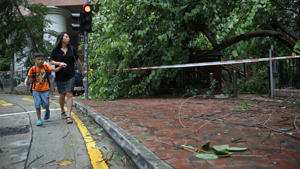 People walk past tree branches broken by strong winds caused by Typhoon Nida in Hong Kong (AP)