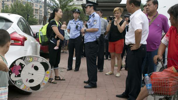 Yuan Shanshan, left, the wife of detained Chinese lawyer Xie Yanyi, is questioned by a police officer near the Tianjin No 2 Intermediate People's Court (AP)